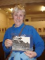 Jane is holding a photo of the MGA outing to Alderley Edge in 1952